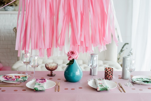Birthday table setting in pink and colors with rose in vase. streamers garland background. baby shower, girl party decoration.