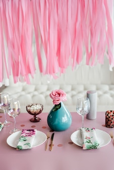 Birthday table setting in pink and colors with rose in vase. streamers garland background. baby shower or girl party.