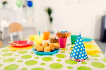 色のついた帽子付きの誕生日のテーブル