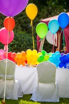 День рождения стол с воздушными шарами радуги. летний отдых в парке. Premium Фотографии