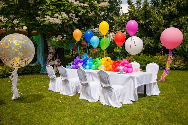 무지개 풍선 생일 테이블. 공원에서 여름 휴가.