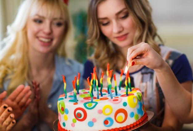 생일. 여자 아이들이 케이크 위에 촛불을 켜고 있습니다.