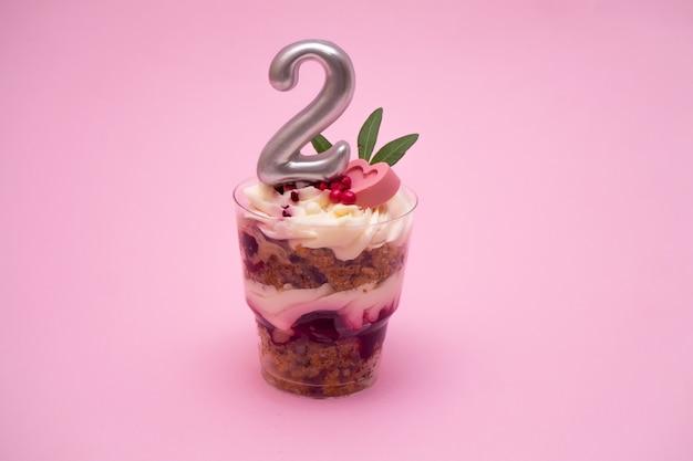 촛불로 표시된 번호 2가있는 생일 사소한 케이크