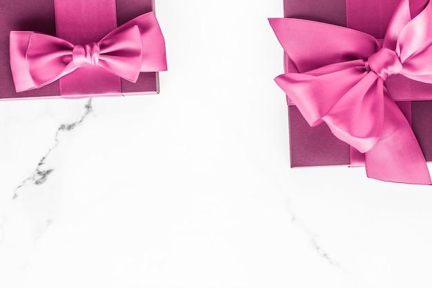 誕生日の結婚式とガーリーブランディングコンセプトピンクのギフトボックス、大理石の背景にシルクのリボンが付いた女の子b ...