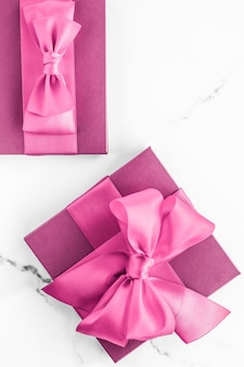 誕生日の結婚式とガーリーブランディングコンセプトピンクのギフトボックス、大理石の背景にシルクの弓、女の子のベビーシャワーのプレゼント、豪華な美容ブランドの休日のフラットレイアートデザインの魅力的なファッションギフト
