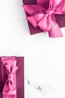 День рождения, свадьба и девчачий брендинг, розовая подарочная коробка с шелковым бантом на мраморном фоне, подарок на детский душ для девочки и гламурный модный подарок для роскошного бренда красоты, праздничный плоский арт-дизайн