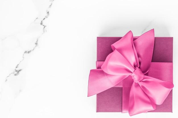 День рождения, свадьба и девчачий брендинг, розовая подарочная коробка с шелковым бантом на мраморном фоне, подарок на детский душ для девочки и гламурный модный подарок для роскошного бренда красоты, праздничный плоский дизайн