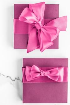 생일 결혼식과 만나고 브랜딩 개념 대리석 배경에 실크 활과 핑크 선물 상자 소녀 베이비 샤워 선물 및 럭셔리 뷰티 브랜드 휴가 flatlay 아트 디자인을위한 매력적인 패션 선물