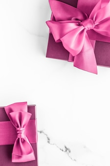 Birthday wedding and girly branding concept  pink gift box with silk bow on marble surface girl baby shower present and glamour fashion gift for luxury beauty brand holiday flatlay art design