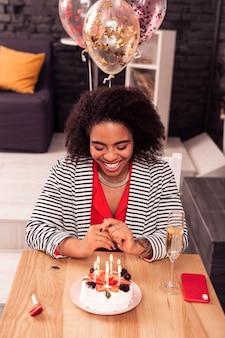 생일 소원. 생일 소원을 만드는 동안 촛불 케이크를보고 행복 긍정적 인 여자