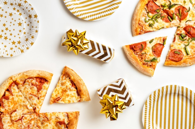 Birthday with junk food. two large tasty pizzas with pepperoni and cheese on a white plate. gifts on the holiday table. top view with copy space for text. flat lay