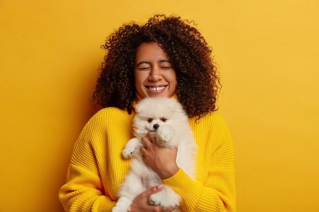 생일 여자가 넓게 웃고, 사랑스러운 애완 동물을 선물로 받고, 오랜 시간 동안 스피츠를 꿈꾸며, 노란색 점퍼를 입고, 실내에 서 있습니다.