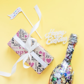 Birthday writing near present and confetti bottle