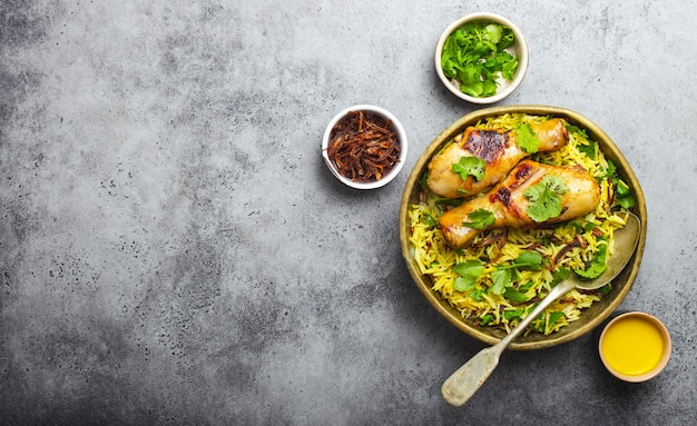 Biryani chicken, traditional dish of indian cuisine, with basmati rice, fried onion, fresh cilantro in bowl on gray rustic stone background. authentic indian meal, top view, close-up, space for text