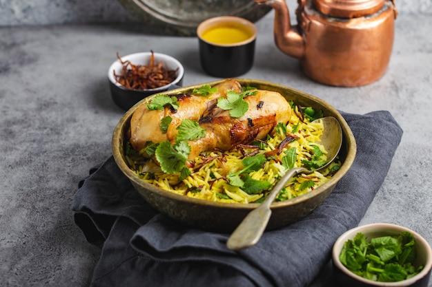 ビリヤニチキン、インド料理の伝統的な料理、バスマティライス、揚げタマネ、灰色の素朴な石の背景にボウルに新鮮なコリアンダー。本物のインド料理、クローズアップ、選択的な焦点