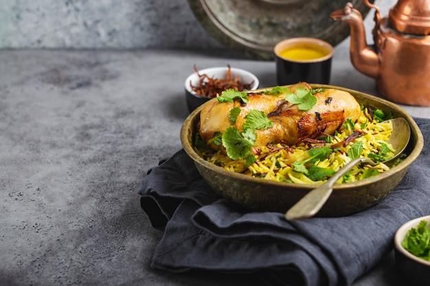 ビリヤニチキン、インド料理の伝統的な料理、バスマティライス、揚げタマネ、灰色の素朴な石の背景にボウルに新鮮なコリアンダー。本物のインド料理、クローズアップ、テキスト用のスペース