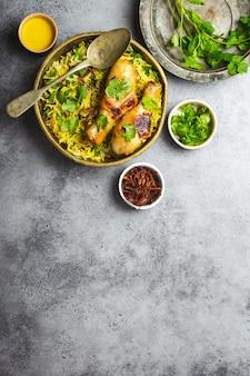 ビリヤニチキン、インド料理の伝統的な料理、バスマティライス、揚げタマネ、灰色の素朴な石の背景にボウルに新鮮なコリアンダー。本物のインド料理、上面図、クローズアップ、テキスト用のスペース