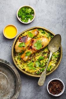 ビリヤニチキン、インド料理の伝統的な料理、バスマティライス、揚げタマネ、灰色の素朴な石の背景にボウルに新鮮なコリアンダー。本物のインド料理、上面図、クローズアップ