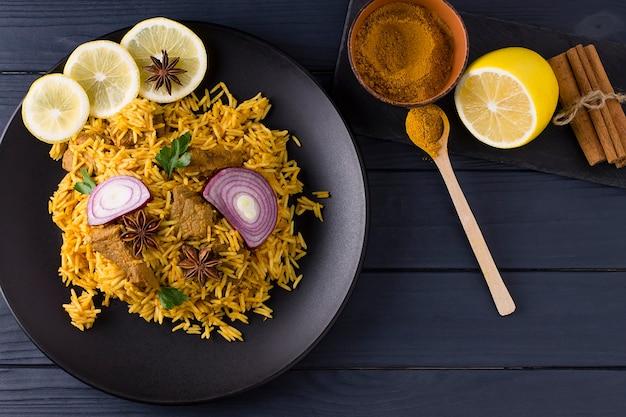 닭고기와 함께 biryani. 쌀과 닭고기, 향신료와 레몬의 전통적인 인도 요리. 나무 배경. 평면도