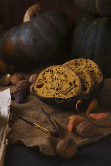 Biscotti cake with nuts, chocolate and pumpkin on a dark table