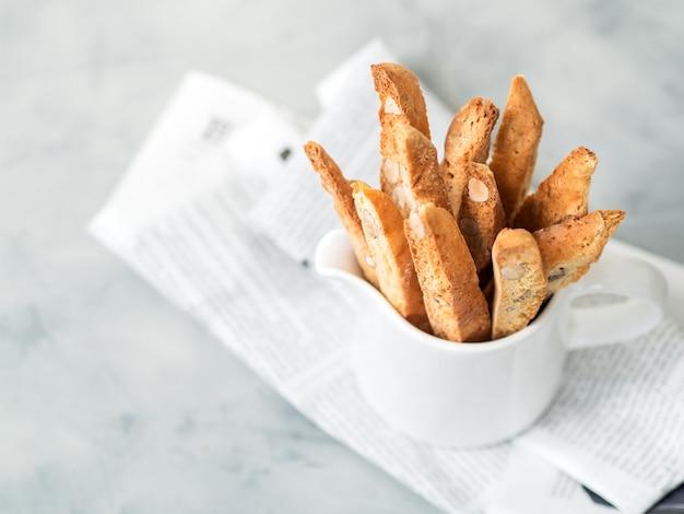Бискотти (cantuccini) - традиционный итальянский миндальный десерт в чашку белого крупным планом.