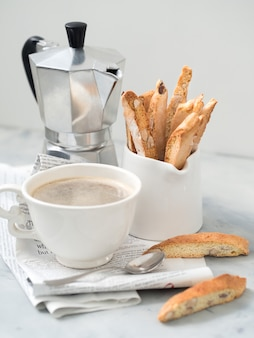 Biscotti - traditional italian almond dessert with cup of coffee and moka coffee pot on newspaper.