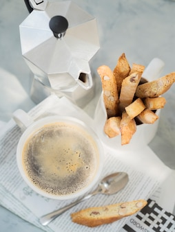 Biscotti traditional italian almond dessert with cup of coffee and moka coffee pot on newspaper.