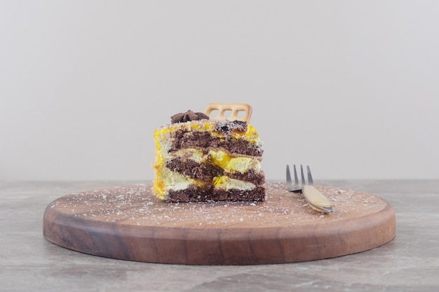 대리석 보드에 포크 옆에 케이크 조각에 비스킷과 아니스