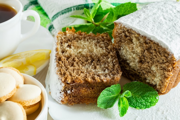 Biscuit cake, a cup of tea with lemon, small cookies and mint leaves on a white wooden table.