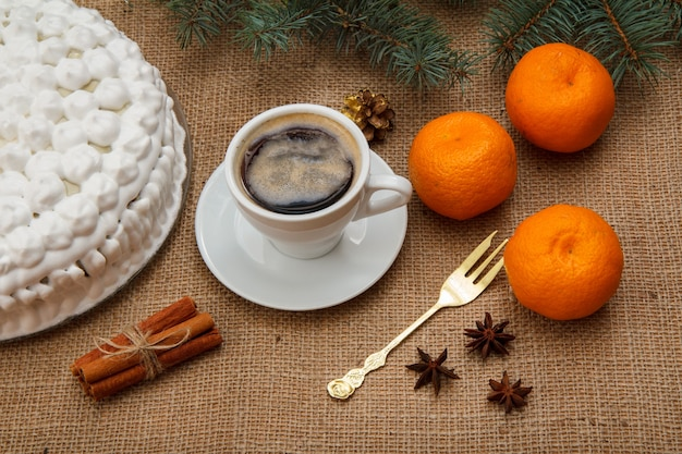 ホイップクリーム、一杯のコーヒー、フォーク、オレンジ、スターアニス、シナモンで飾られたビスケットケーキ。荒布にトウヒの枝が付いています。上面図。メリークリスマスのコンセプト。