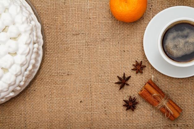 ホイップクリーム、一杯のコーヒー、オレンジ、スターアニス、シナモンで飾られたビスケットケーキと荒布。上面図。
