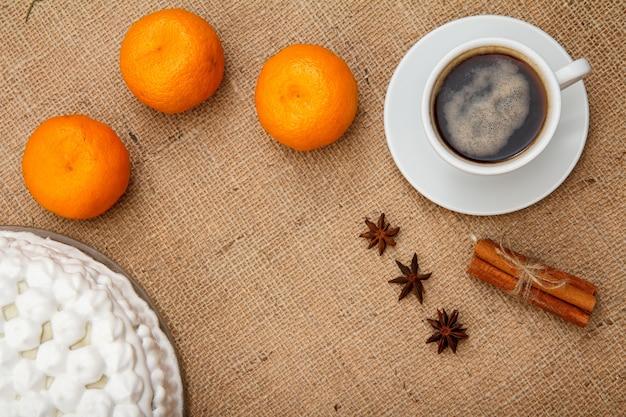 ホイップクリーム、一杯のコーヒー、オレンジ、スターアニス、荒布を着たテーブルの上のシナモンで飾られたビスケットケーキ。上面図。