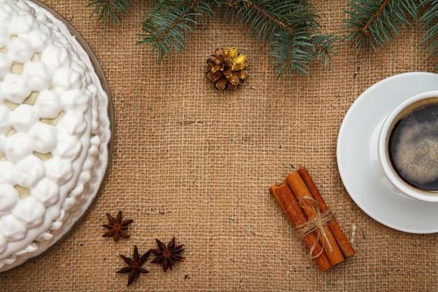 ホイップクリーム、一杯のコーヒー、スターアニス、シナモンで飾られたビスケットケーキ。荒布にトウヒの枝が付いています。上面図。メリークリスマスのコンセプト。