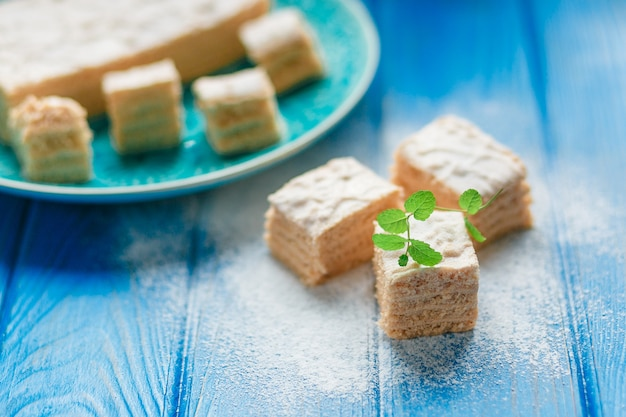 Biscuit cake pie apple candy pastila, mint leaves on blue wood cutting board background.
