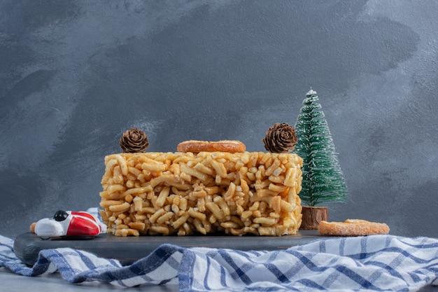 Torta biscotto con biscotti a fiocchi e ornamenti natalizi su una tavola sulla superficie di marmo