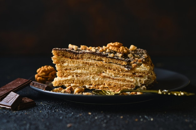 Biscuit cake with sour cream, nuts and chocolate glaze, on a black plate with chocolate on a dark textured background, selective focus