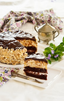 Biscuit chocolate cake witn meringue layer, buttercream filling chocolate glaze