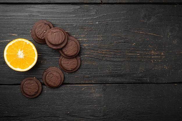 주황색으로 채워진 비스킷, 초콜릿 세트를 얹은 검은색 나무 테이블 배경, 위쪽 뷰 플랫 레이, 텍스트 복사 공간