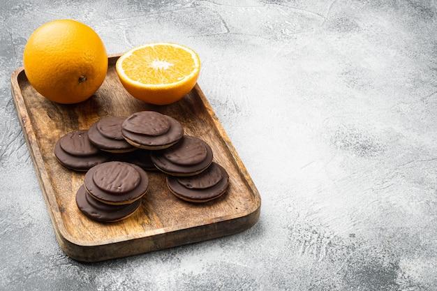 주황색으로 채워진 비스킷, 초콜릿 세트를 얹은 회색 배경, 텍스트 복사 공간