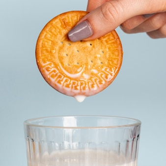 Biscuit held above glass of milk close-up
