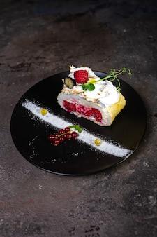 Бисквитный рулет с ягодами на стильной черной тарелке