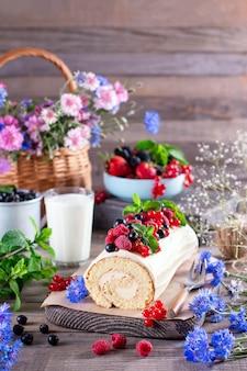 Бисквитный рулет с кремом маскарпоне и ягодами, листьями мяты на деревянных фоне. концепция летней еды