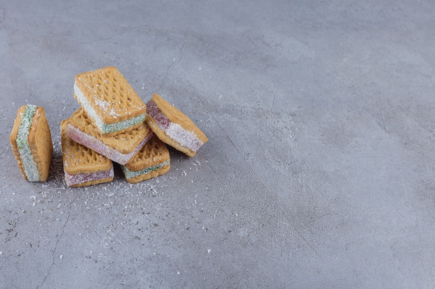 Biscuit sandwich filled with colorful marmalade on stone background.