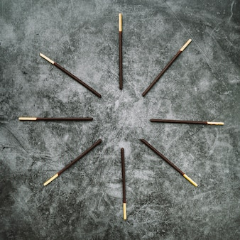 Biscuit stick deep in chocolate arranged in circular on stained concrete background