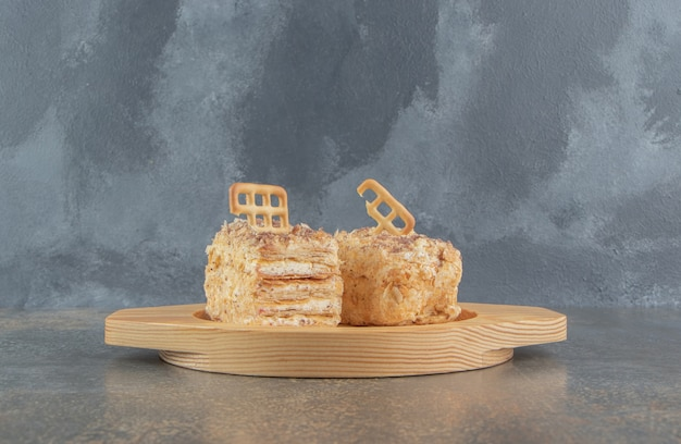 木製の大皿にケーキのスライスをトッピングするビスケット
