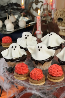 Бисквит с мозгами и капкейки в шоколадной глазури, украшенные марципановыми привидениями на хэллоуин