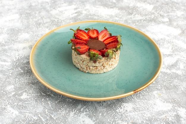 Бисквит с клубникой и круглым шоколадом на синей тарелке