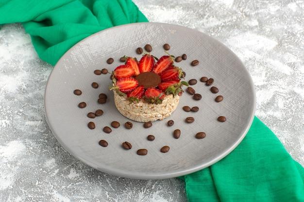 イチゴと紫色のプレートの中に丸いチョコレートが入ったビスケットとコーヒーの種子