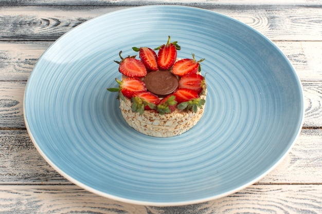 Biscuit with strawberries and round chocolate inside blue plate on rustic grey