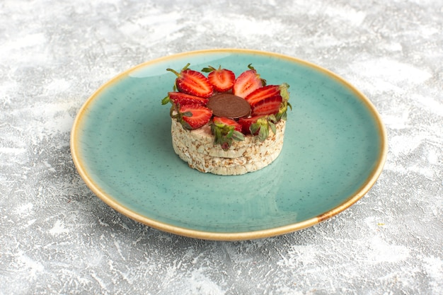 Biscuit with strawberries and round chocolate inside blue plate